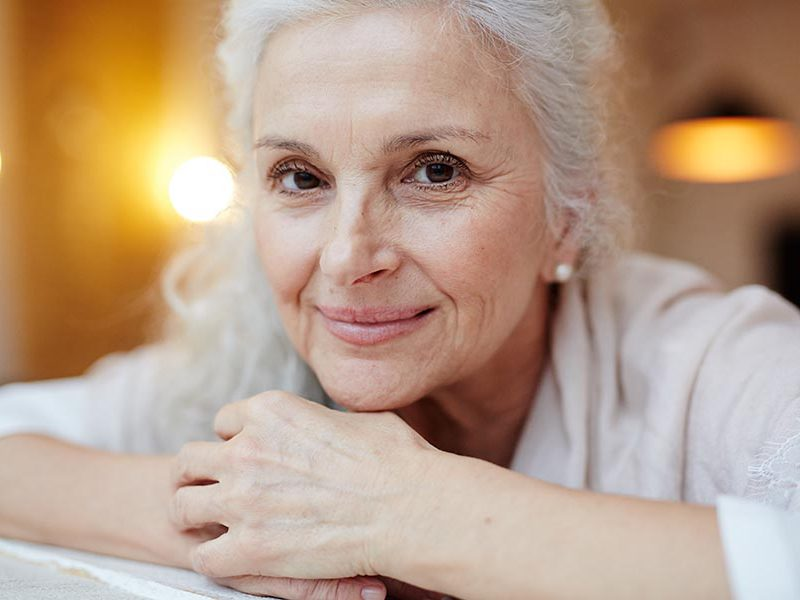Happy grey-haired female smiling at camera
