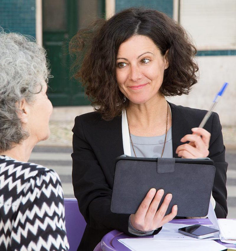 Smiling young consultant offering pen to elderly client for signing documents. Senior grey haired lady talking to young positive woman in jacket with tablet and pen. Agent work concept
